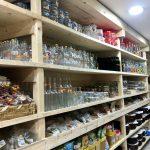 Bottiglie, barattoli e contenitori in vetro di verse forme e colori.