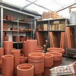 Reparto di vasi in plastica, fioriere in ferro battuto.